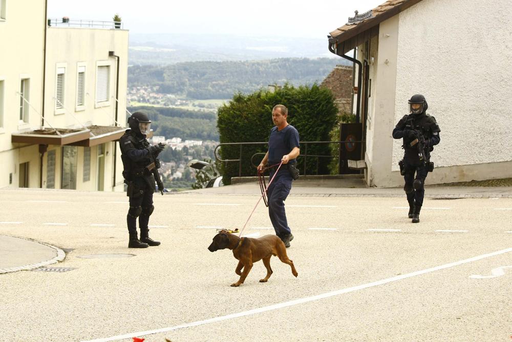 FOTO: PETER GERBER, 04.02.2010, Leublingen (BE):Unterhalb von Magglingen im Dorf Leublingen sperrte die Sondereinheit der Polizei kurz die Strasse, zwei Schwerbew. beschŸtzten einen Bluthund der Polizei und dessen FŸhrer, der Hund schnupperte in einer TŸte und suchte die Spur vom Amok Senior aus Biel. Amok Biel